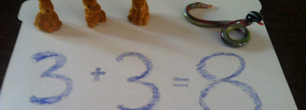 Zwei Deko-Osterhäschen sitzen auf einem Blatt Papier, auf dem mit blauer Farbe Zahlen aufgemalt sind in Form einer Gleichung 3+3=8.