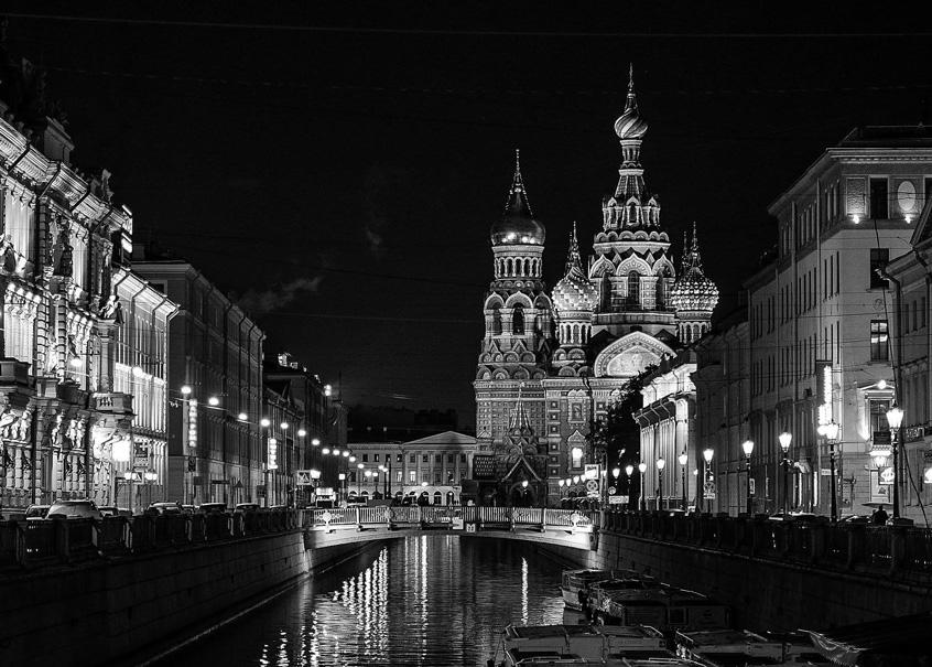 Die Basilius-Kathedrale in Moskau bei Nacht. Sie ist hell angestrahlt, ebenso wie die prachtvollen Häuserfassaden entlang eines Kanals, der auf die Kirche zuläuft.
