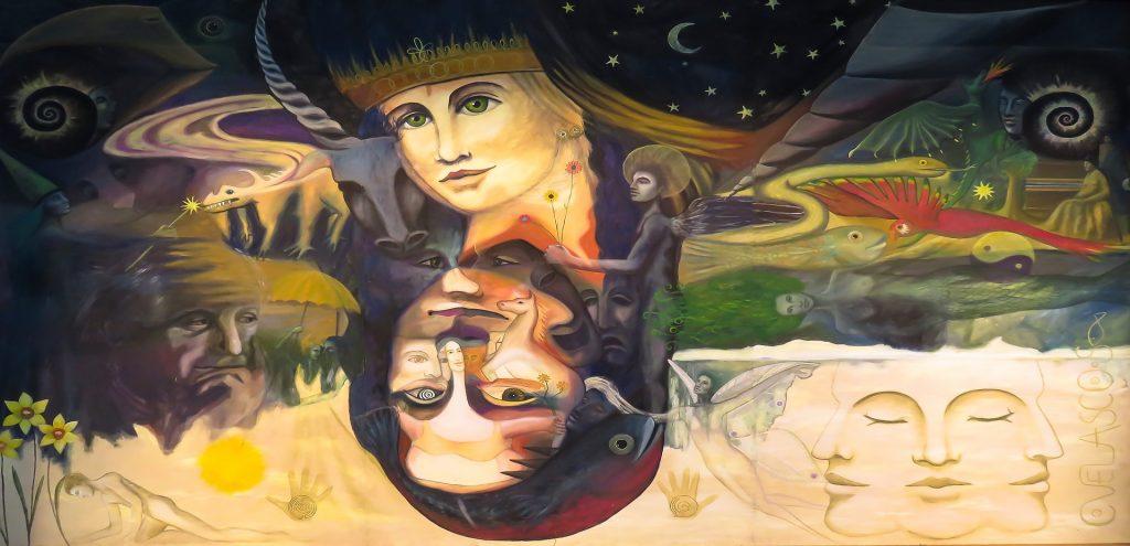 Vor einem dunkelblauen Sternenhimmel mit zartgelber Mondsichel sieht man verschieden Gesichter und Figuren: Ein Frauengesicht mit einer Krone, ihr gespiegelt ein Frauengesicht mit schwarzen Haaren, ein schwarzer Engel mit Heiligenschein, eine fliegende, sehr helle Figur, ein weißes Pferd, ein Fisch, ein Handabdruck und zwei Masken, dazu einen grünen Farbfleck.