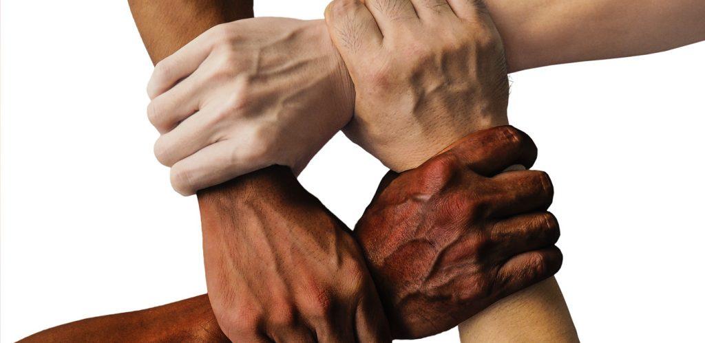 Vier Hände mit unterschiedlichen Hautfarben umfassen sich gegenseitig so an den Handgelenken, dass sie ein Viereck bilden.