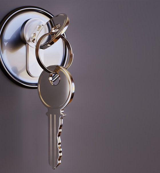 In einem glänzenden, silbernen Schloss steckt ein ebenfalls glänzender, silberner Schlüssel, an dem an einem Ring ein zweiter Schlüssel hängt.