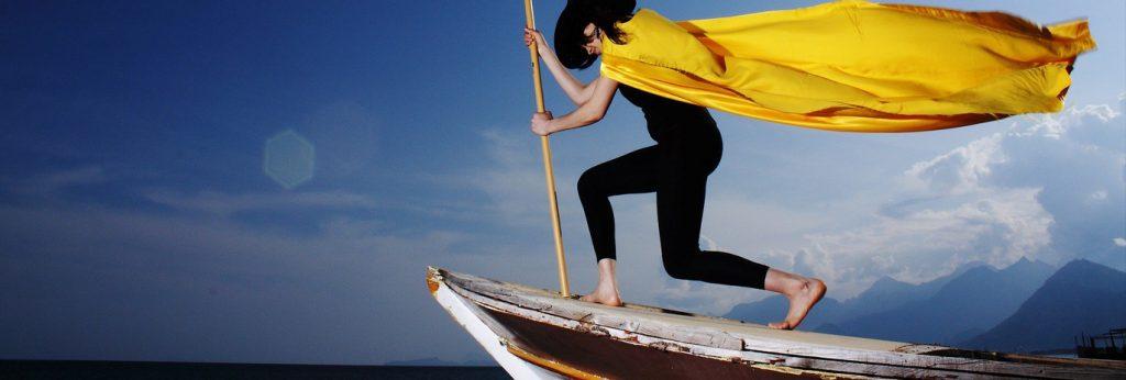 Eine schlanke junge Frau, die ein enges schwarzes Trikot, einen schwarzen, großen Hut und einen wehenden, leuchtend gelben Umhang trägt, steht auf dem Bug eines Bootes und schwenkt eine große schwarze Fahne. Sie fährt über ruhiges Wasser gegen einen blauen Himmel.