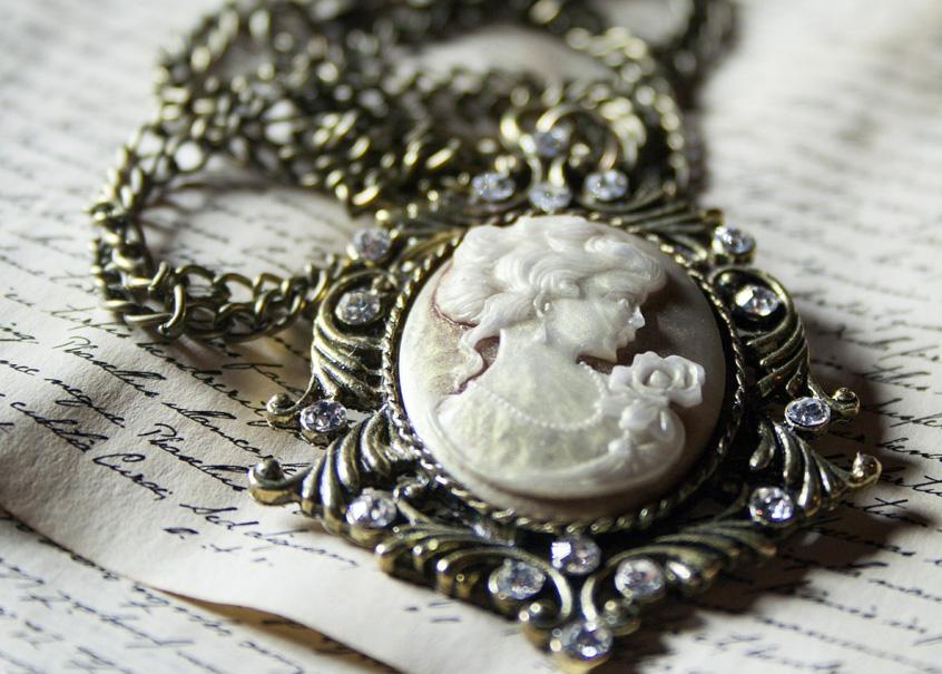 Ein reichverzierter silberner Kettenanhänger, der mit einem aus Perlmutt geschnitzten, sehr zierlichen und hübschen Kopf einer jungen Frau geschmückt ist, liegt auf einem handgeschriebenen Manuskript, vielleicht einem Brief.
