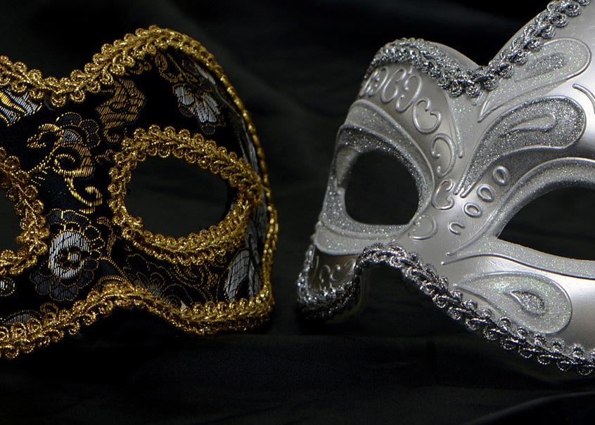 Zwei halbe venezianische Augenmasken liegen sich auf schwarzem Samt so gegenüber, dass sie ein Ganzes bilden. Sie sind beide mit Ornamenten bestickt, die eine Maske ist silbern, die andere schwarz und mit goldenen Säumen verziert.