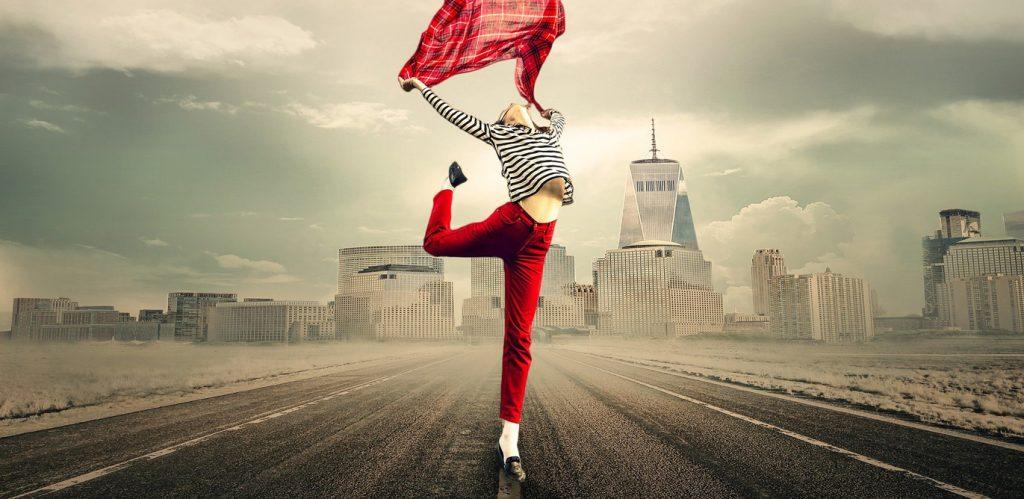Eine schlanke junge Frau in einer roten Hose und einem blauweiß gestreiften Oberteil tanzt ekstatisch auf einer sehr breiten Straße vor einer Großstadt-Silhouette. Sie reckt das rechte Bein nach hinten hoch in die Luft und schwenkt ein rot kariertes Tuch mit beiden Armen über ihrem Kopf.