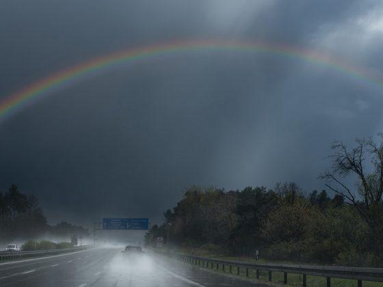 Ein Regenbogen überspannt eine breite Autobahn, der Himmel ist bedrohlich dunkelgrau.