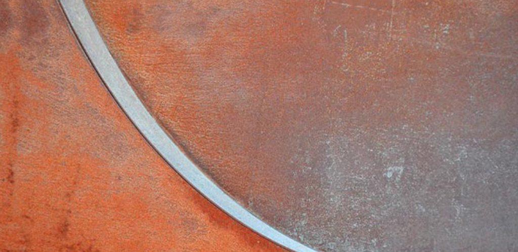 Das Bild ist ausgefüllt von einer rostroten Fläche, die von links oben nach rechts unten durchbrochen wird von einem mondsichelförmigen, fast weißen, schmalen Streifen, der sich nach unten hin zuspitzt. Oberhalb dieser Zuspitzung verfärbt sich das Rostrot zu einem verwaschenen Grau. Das Bild strahlt eine geheimnisvolle Harmonie aus.