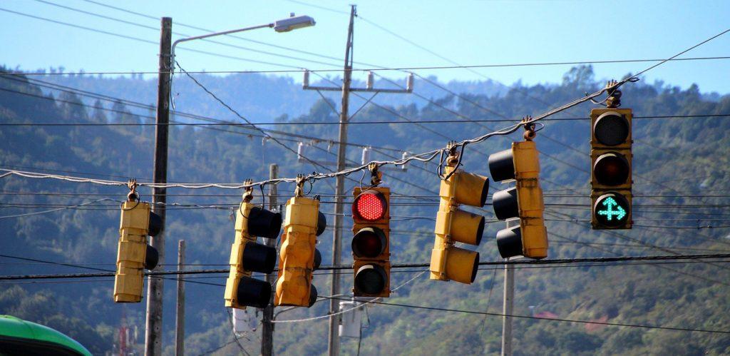 """Vor einer gebirgigen, bewaldeten Landschaft im Hintergrund, hängen an einem Kabel sechs Ampeln nebeneinander, die in verschiedene Richtungen zeigen. Eine der Ampeln ist auf """"Rot"""" gestellt, doch die ganze Ampelanlage wirkt völlig ungeeignet, den Verkehr zu regeln, sondern sieht eher so aus, als würde sie großes Durcheinander verursachen."""