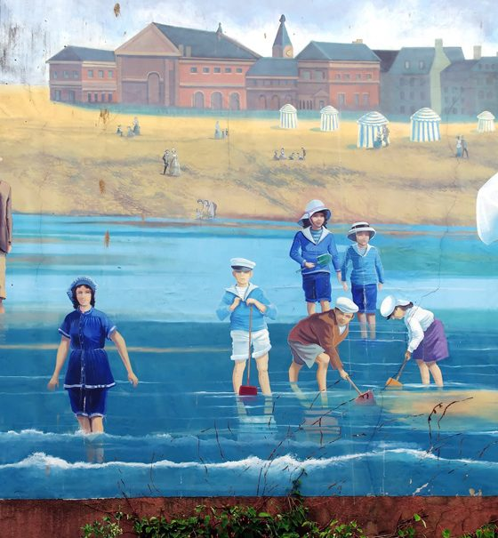 In einem Seebad in der Normandie vergnügen sich mehrere Menschen in Kleidern der Belle Epoque am Meer.