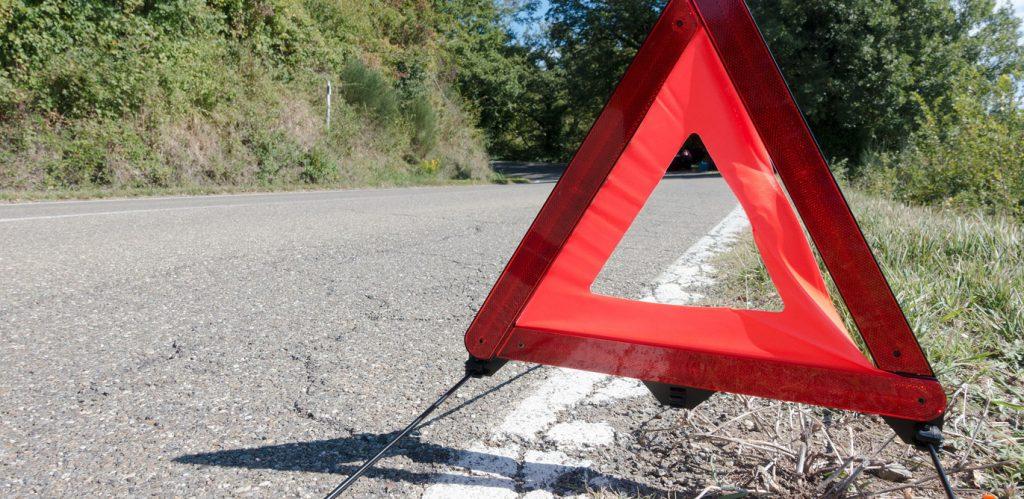 Auf einer geteerten Straße steht ein rotes Warndreieck.